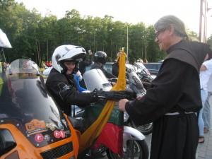 Asta Mačiulaitienė (kairėje)  po kelionės  perduoda br. Benediktui OFM  prezidentės dovanotą vėliavą